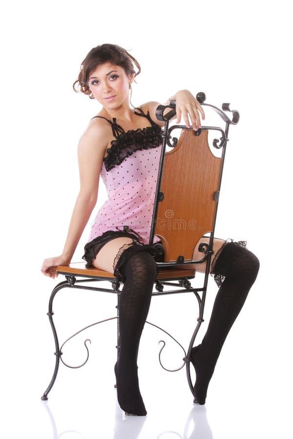 Frau im Rosa, das einen Stuhl spreizt lizenzfreie stockfotos