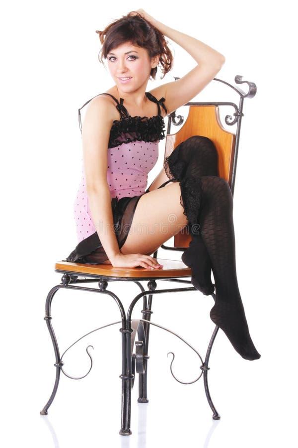 Frau im rosafarbenen Sitzen auf Stuhl sideview stockfotos