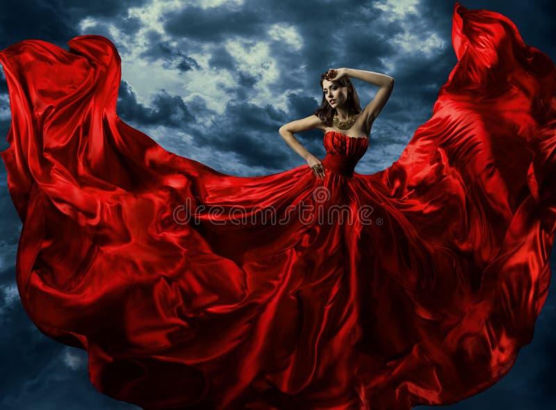 Frau im roten Abendkleid, wellenartig bewegendes Kleid mit dem Fliegen des langen Gewebes stockfotos