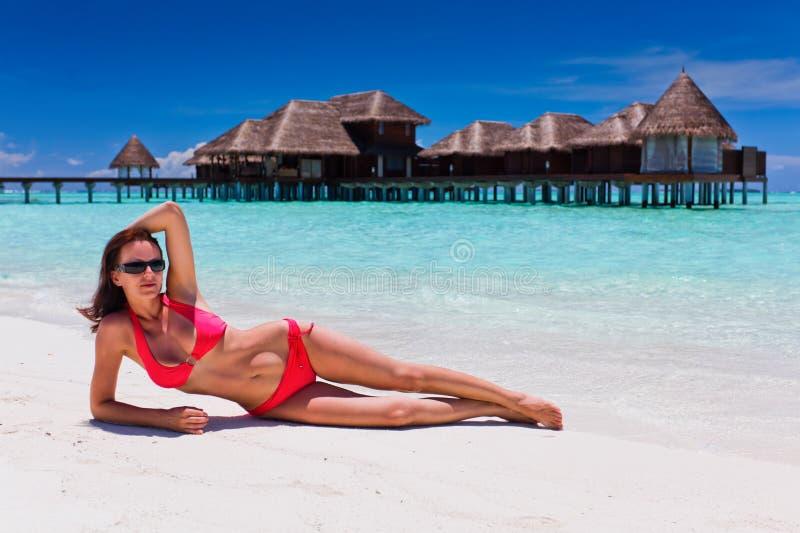 Frau im roten Bikini in der Strandzieleinheit stockbilder