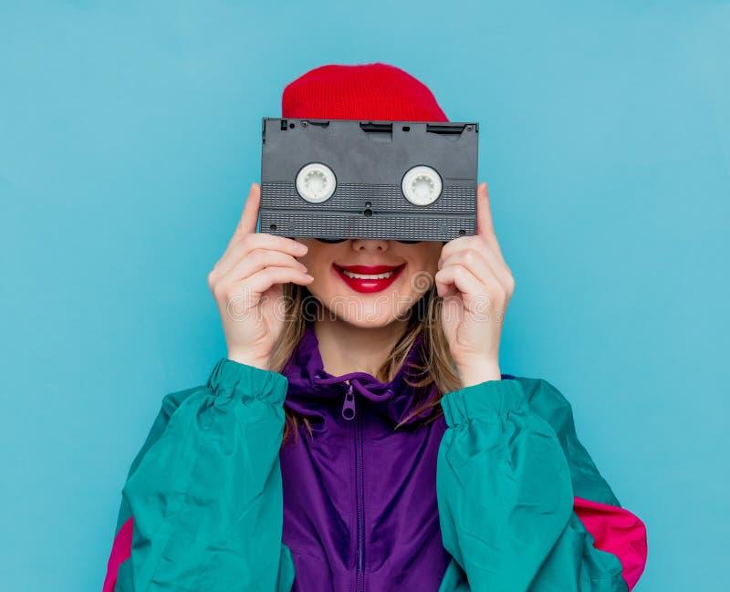Frau im roten Hut, in der Sonnenbrille und im Anzug von 90s mit VHS-Kassette lizenzfreie stockfotos