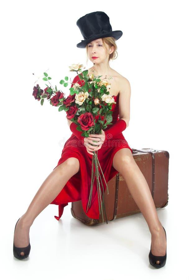 Frau im roten Kleid mit einem Blumenstrauß der Blumen stockbild
