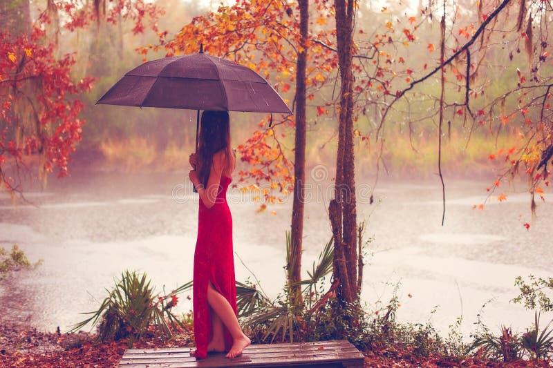 Frau im roten Kleid mit Regenschirm stockbilder