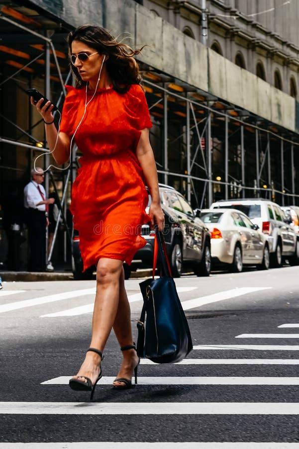 Frau im roten Kleid mit Smartphoneüberfahrtstraße in New York lizenzfreie stockbilder