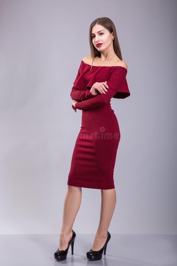 Frau im roten Kleid und in den roten Lippen über grauem Hintergrund stockfoto