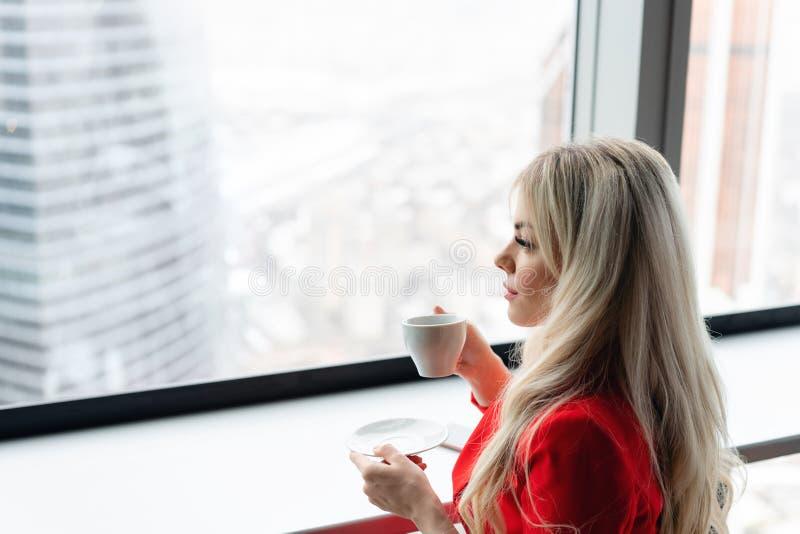 Frau im roten korallenroten Anzug trinkt Kaffee an einem hohen Tisch nahe dem Fenster Junge blonde Geschäftsfrau im Büro lizenzfreie stockbilder
