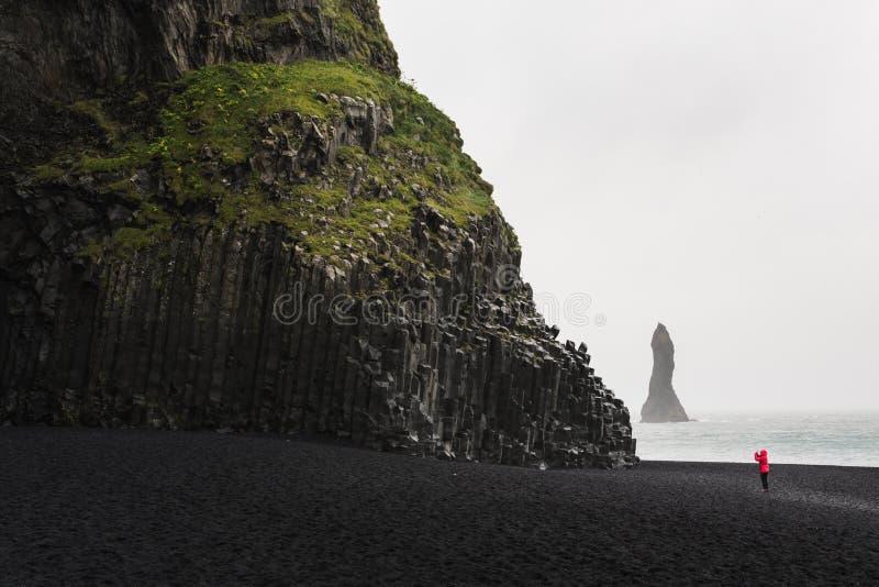 Frau im roten Regenmantel, der Fotos der schwarzen Basaltsäulen am schwarzen Sandstrand in Vik, Island macht stockfotografie