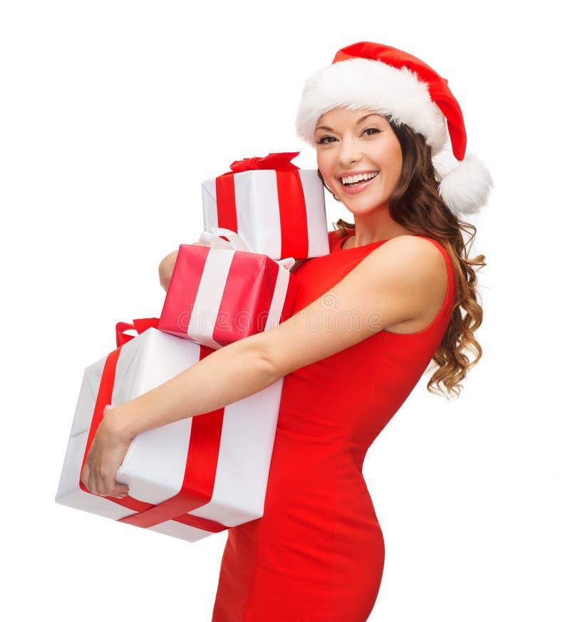 Frau im Sankt-Helferhut mit vielen Geschenkboxen stockbild