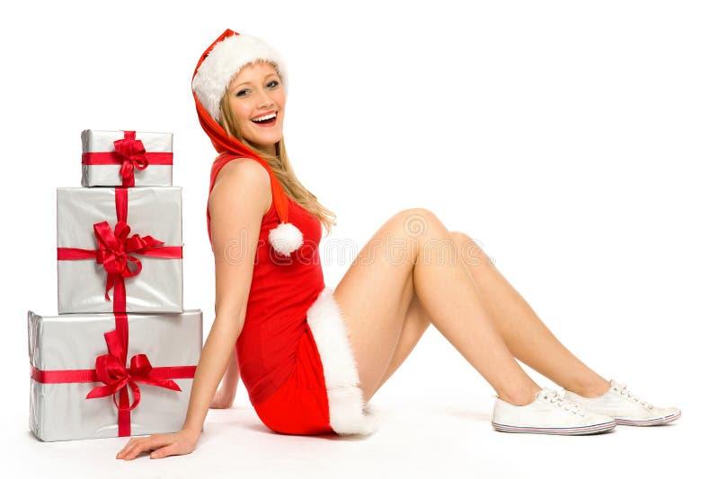 Frau im Sankt-Hut, der nahe Weihnachtsgeschenken sitzt lizenzfreies stockbild