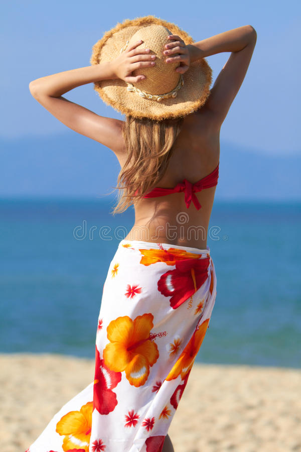 Frau im Sarong und im Strohhut stockfoto