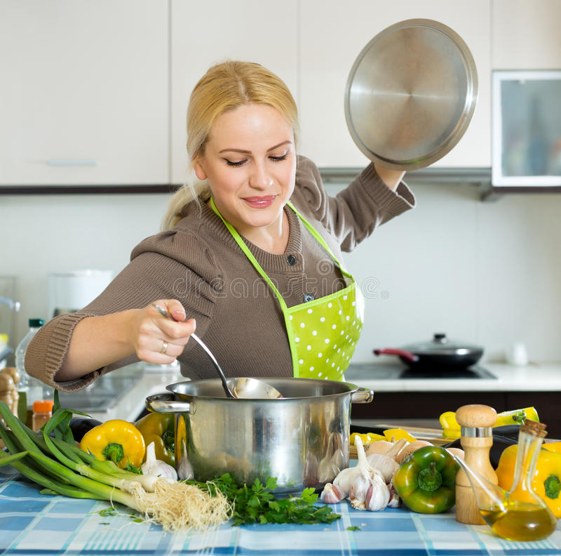Frau im Schutzblech an der Küche stockfotografie