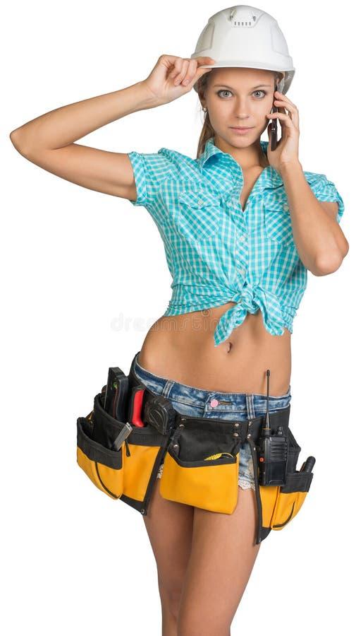 Frau im Schutzhelm und Werkzeug schnallen das Ersuchen um Mobile um lizenzfreies stockbild
