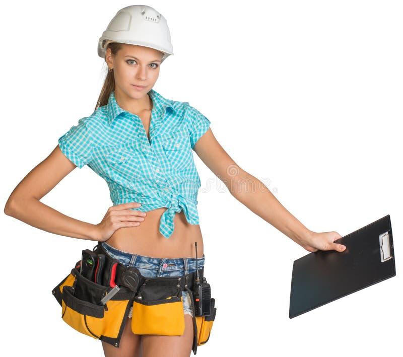 Frau im Schutzhelm und Werkzeug schnallen das Halten des Klemmbrettes um stockbilder