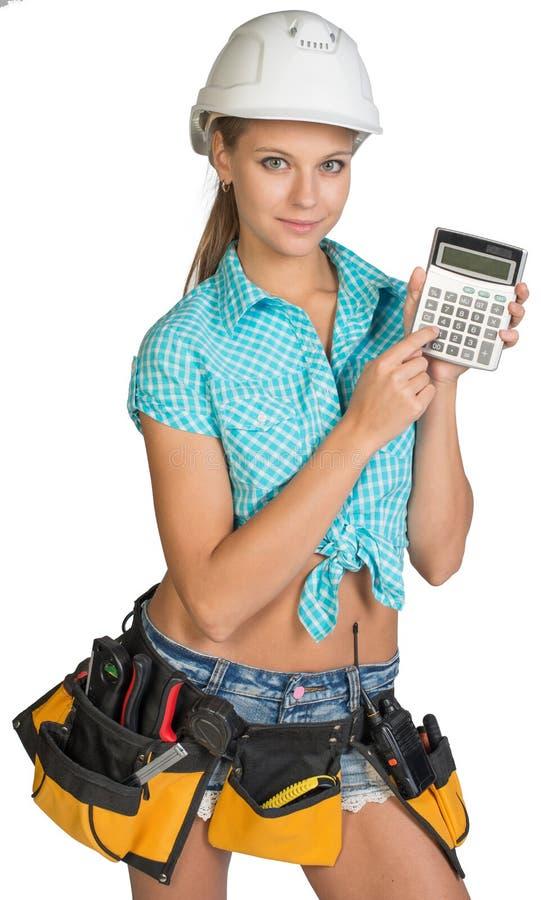 Frau im Schutzhelm und Werkzeug schnallen das Zeigen des Taschenrechners um lizenzfreies stockfoto