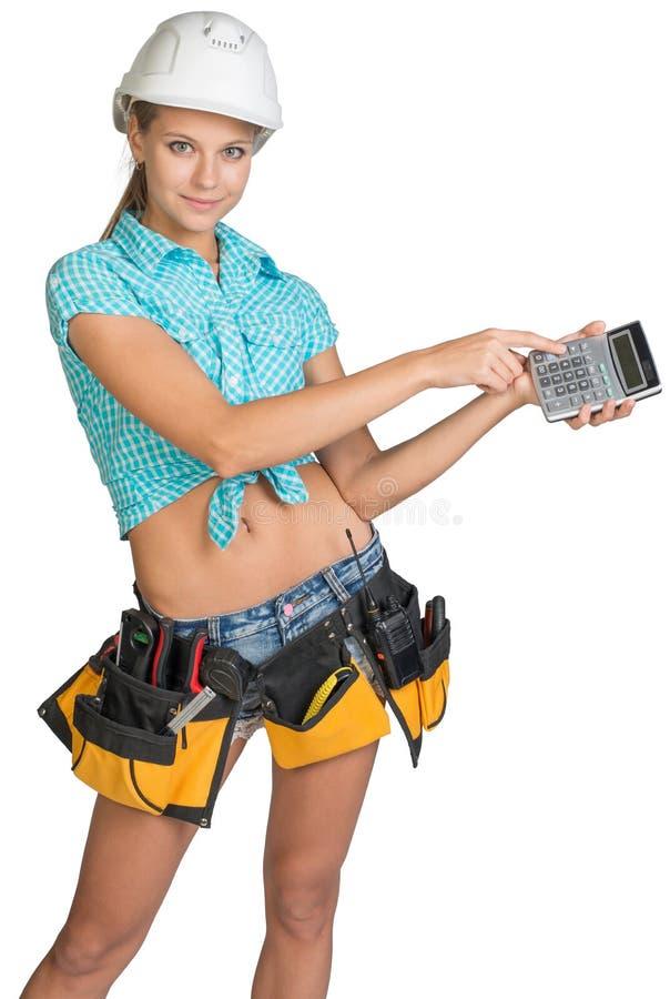 Frau im Schutzhelm und Werkzeug schnallen das Zeigen des Taschenrechners um stockbild
