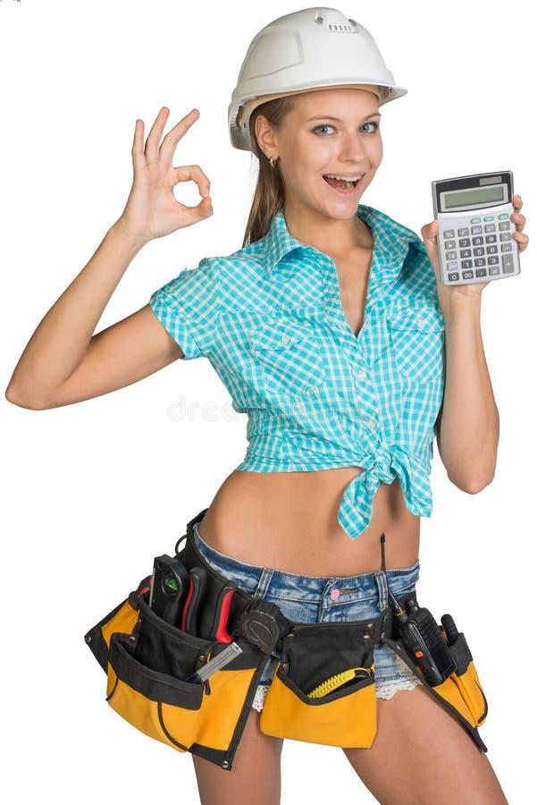 Frau im Schutzhelm und Werkzeug schnallen das Zeigen des Taschenrechners um stockfoto