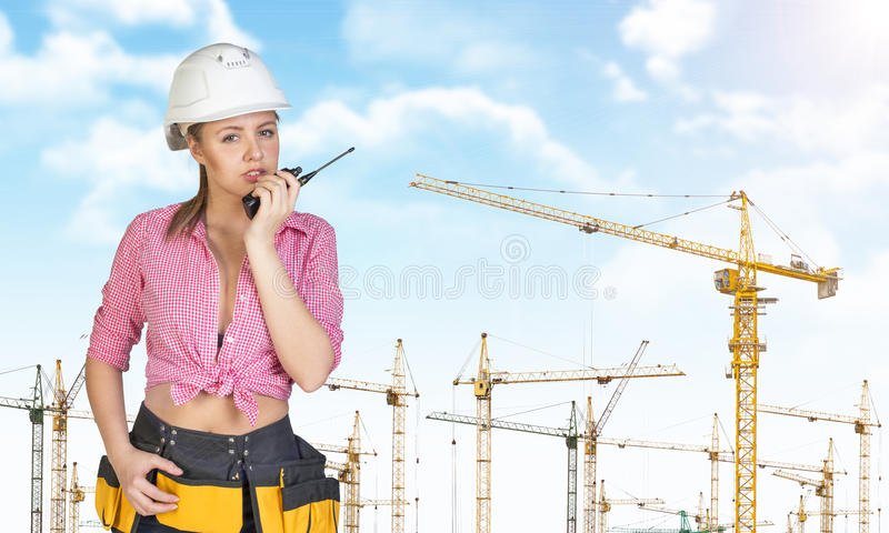 Frau im Schutzhelm und Werkzeug schnallen die Unterhaltung auf walkie um lizenzfreies stockbild