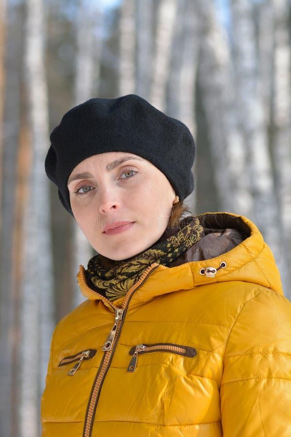 Frau im schwarzen Barett und in einer gelben Jacke. lizenzfreies stockbild