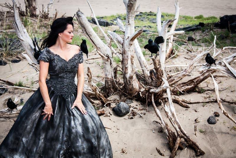 Frau im schwarzen Hochzeitskleid mit Krähen lizenzfreies stockfoto