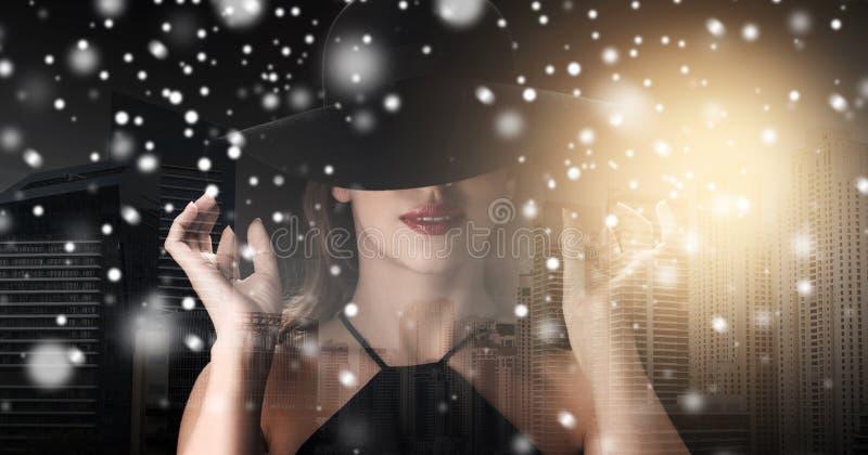 Frau im schwarzen Hut über Stadthintergrund und -schnee lizenzfreie stockfotografie