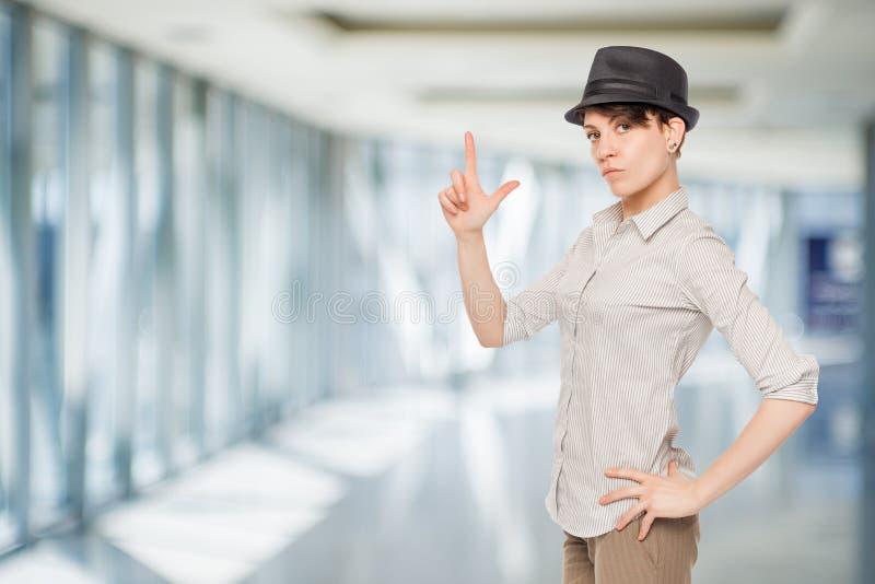 Frau im schwarzen Hut hält Fingergewehr stockfoto