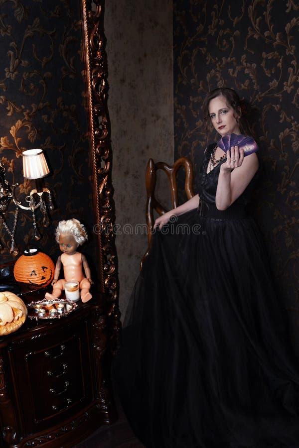 Frau im schwarzen Kleid für Halloween mit einem Fan von Karten in der Hand lizenzfreies stockfoto