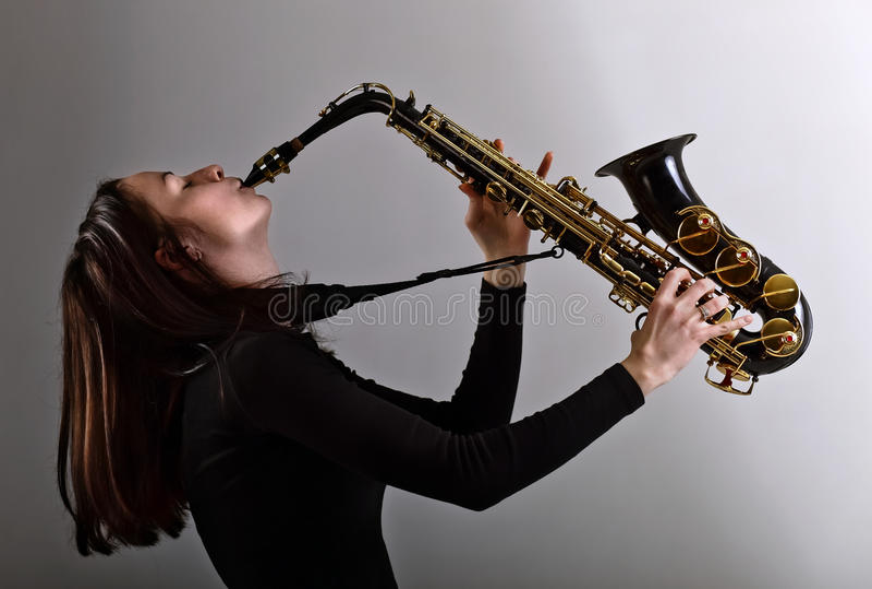 Frau im Schwarzen mit Saxophon stockbild