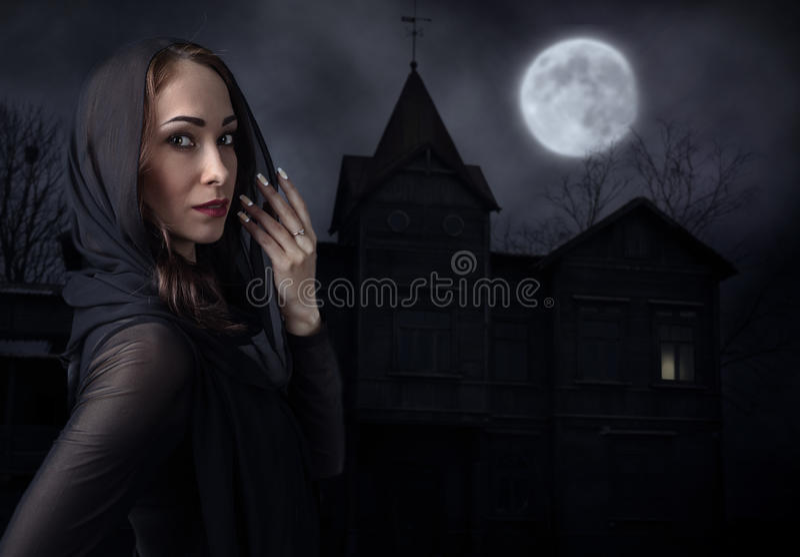 Frau im Schwarzen vor altem Haus auf einer mondbeschienen Nacht lizenzfreies stockbild