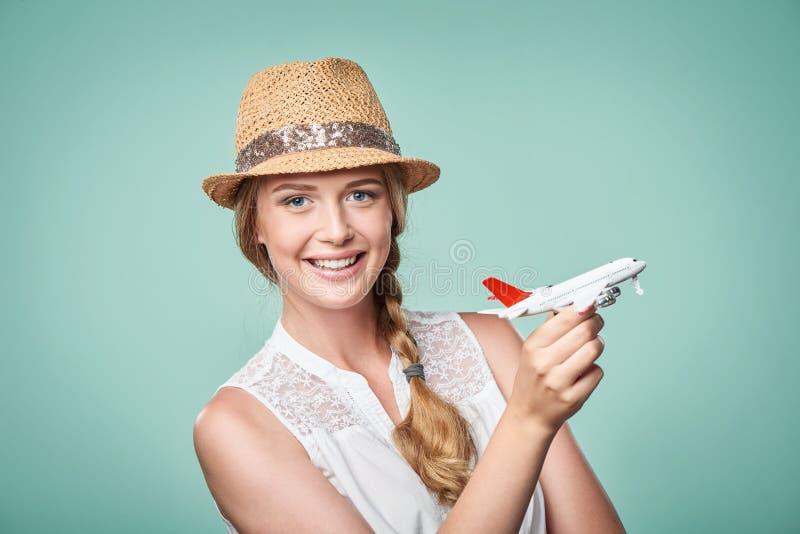 Frau im Strohhut, der in der Hand Flugzeugmodell hält stockfoto