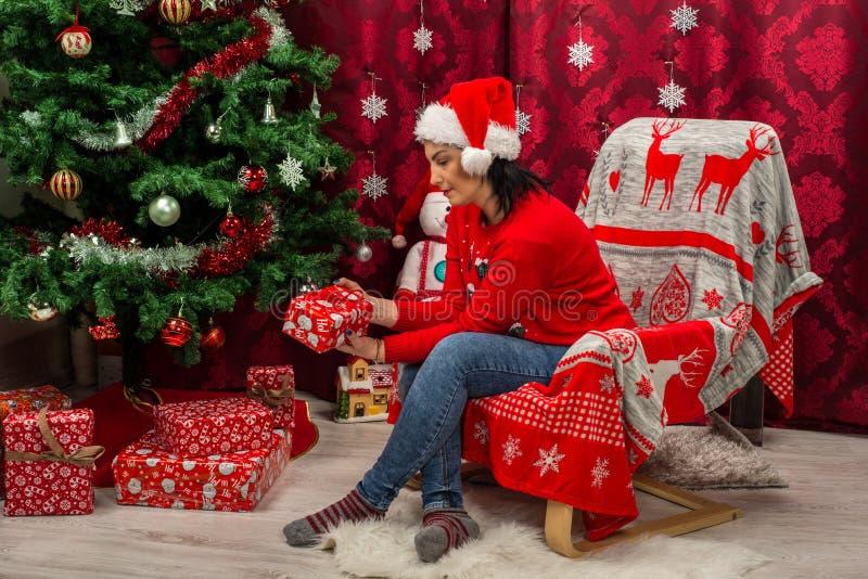 Frau im Stuhl, der Weihnachtsgeschenk betrachtet lizenzfreie stockfotos