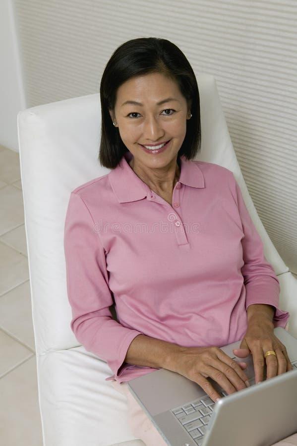 Frau im Stuhl unter Verwendung der hohen Winkelsicht des Laptopporträts stockbild