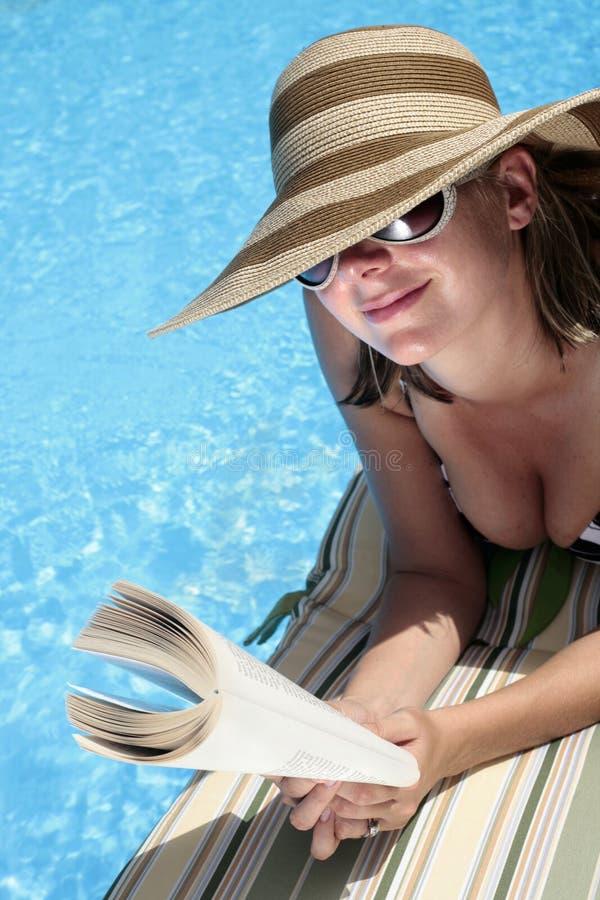 Frau im Sunhat Messwert durch Pool lizenzfreie stockbilder