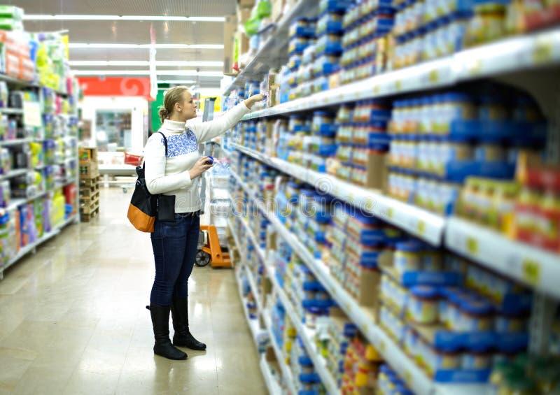 Frau im Supermarkt. Die Nahrung des Kindes. stockbild