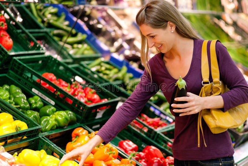 Frau im Supermarkt kauft Gemüse stockfotos