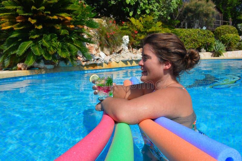 Frau im Swimmingpool mit einem Getränk lizenzfreies stockbild