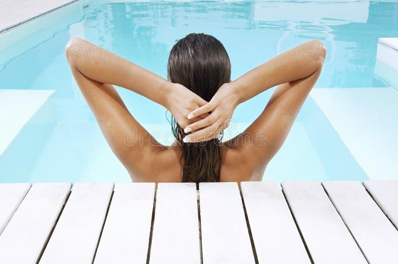 Frau im Swimmingpool am Poolside, der Rückenhaar zieht lizenzfreies stockfoto
