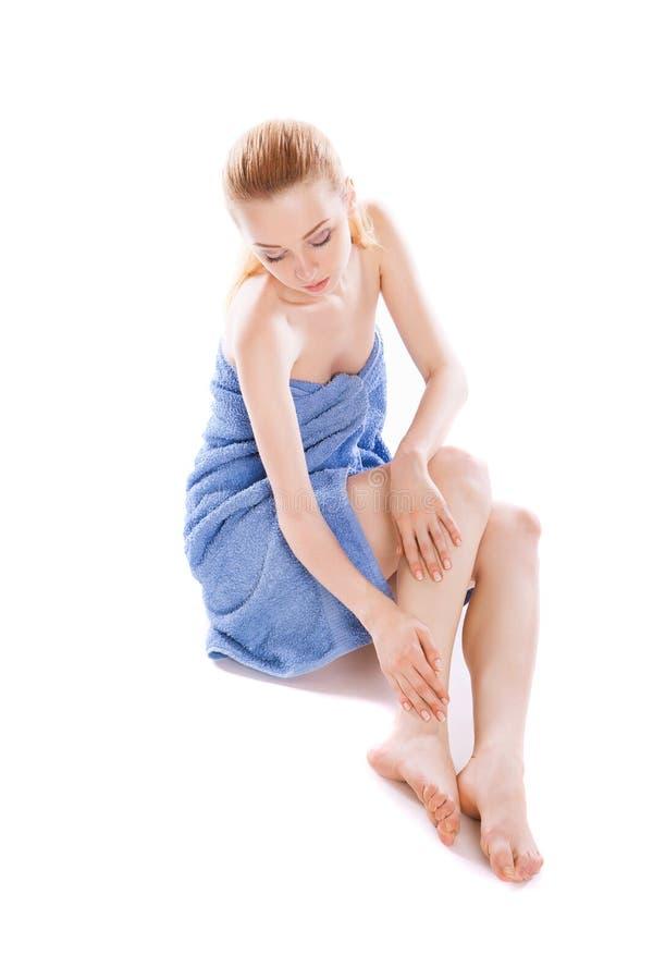 Frau im Tuch, das auf dem Boden, ihre Beine streichend sitzt lizenzfreies stockbild