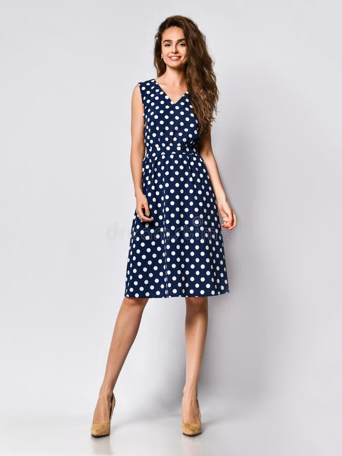 Frau im Tupfen Kleiderin mode Speicher - Portr?t des M?dchens in einem Kleidungsgesch?ft in einem Midi-Sommerkleid lizenzfreie stockbilder