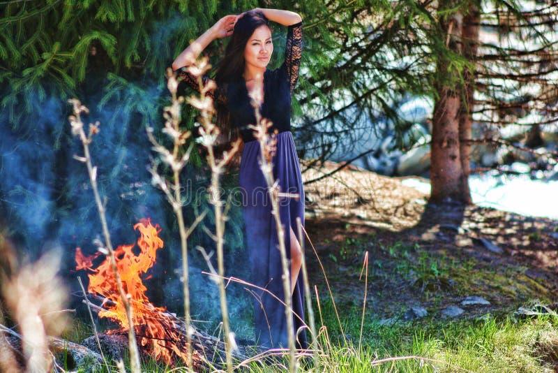 Frau im Wald auf einem Hintergrund des Feuers lizenzfreie stockbilder