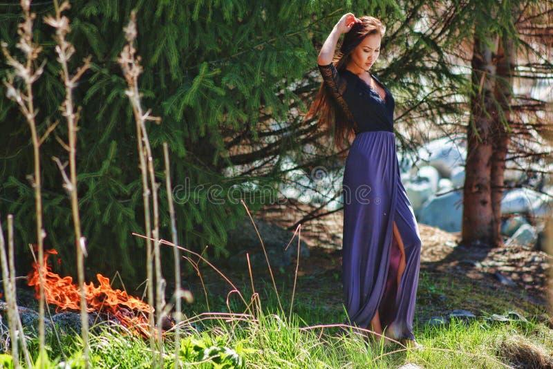 Frau im Wald auf einem Hintergrund des Feuers stockfotografie