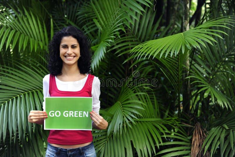 Frau im Wald, der ein gehengrünzeichen anhält stockfotos
