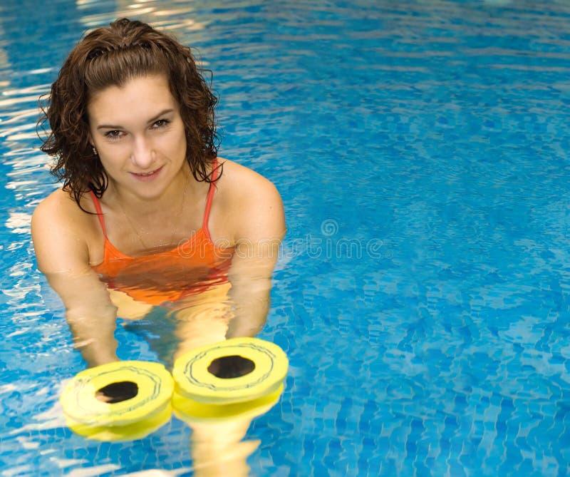 Frau im Wasser mit dumbbels lizenzfreie stockbilder
