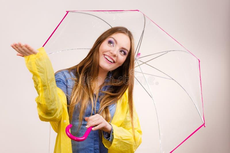 Frau im wasserdichten Mantel mit Regenschirm voraussage stockbild