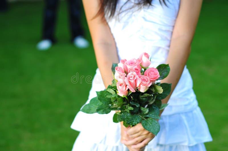 Frau im Weiß, das einen Blumenstrauß der rosafarbenen Blumen anhält lizenzfreie stockbilder