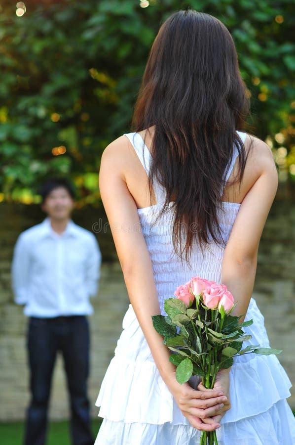 Frau im Weiß, das einen Blumenstrauß der rosafarbenen Blumen anhält stockfotos