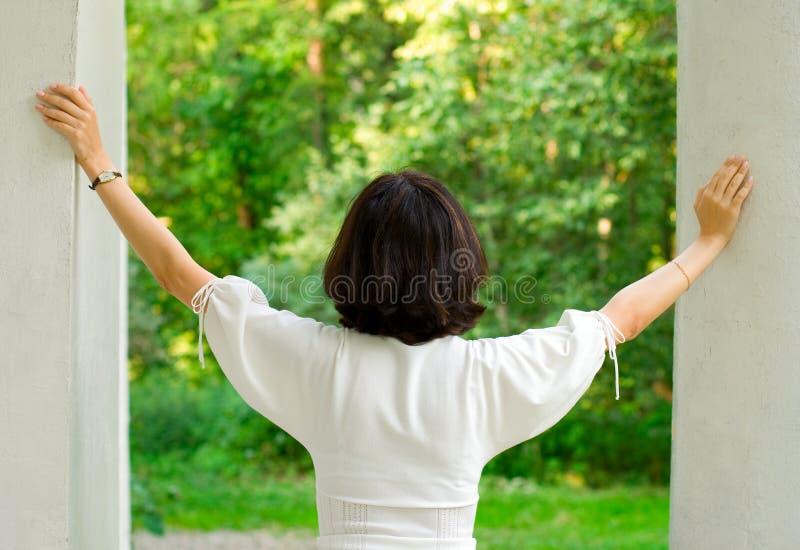 Frau im Weiß, das heraus Fenster schaut lizenzfreie stockbilder