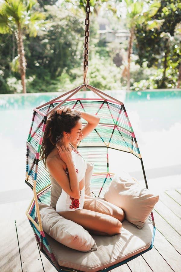 Frau im weißen Badeanzug genießend in hängendem Stuhl stockfotografie