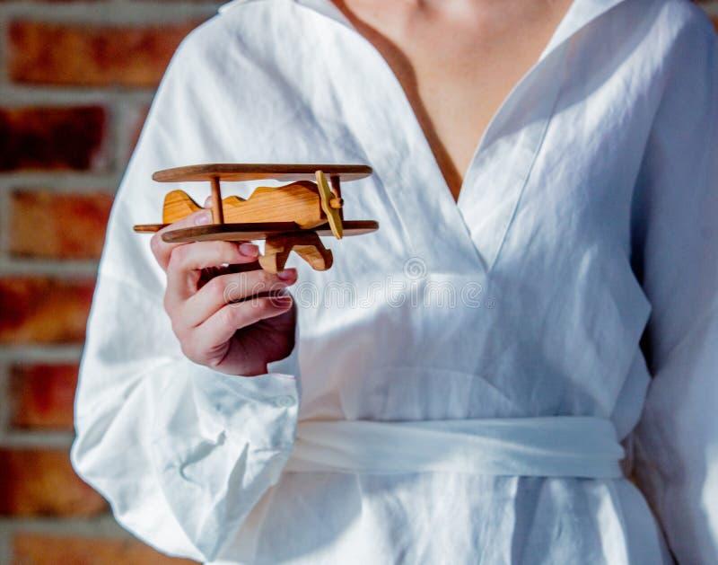 Frau im weißen Hemd, das ein hölzernes Spielzeugflugzeug hält stockbild