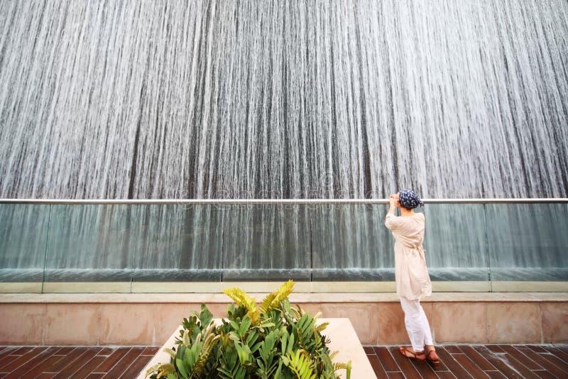 Frau im weißen Hemd, das nahe großem Brunnen steht stockfotos