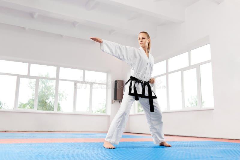 Frau im weißen Kimono mit Trainingskarate des schwarzen Gürtels lizenzfreies stockfoto